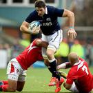 Johnnie Beattie of Scotland is tackled by Nili Latuand Siale Piutau of Tonga during the autumn test international match at Rugby Park