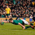 Garry Ringrose of Ireland scores his side's second try despite the tackle of Dean Mumm