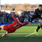 Saracens' Chris Ashton evades a tackle from Munster's Simon Zebo to score his side's third try of the game