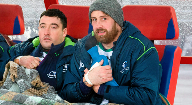 Connacht's Denis Buckley, left, and Aly Muldowney attempt to keep warm on the team bench.