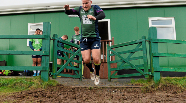 Connacht's Finlay Bealham jumps over a muddy area, at the entrance to the training pitch, before the start of squad training. Sportsground, Galway. Photo: David Maher / Sportsfile
