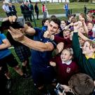 Tiernan O'Halloran poses for pictures with students during Connacht's visit to Seamount College, Kinvara. Picture: INPHO