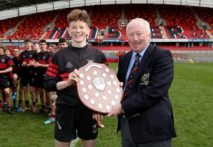 Waterpark's Nick O'Donoghue is presented with the trophy by Munster Rugby President Mick Goggin