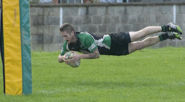 Barry Hynes dives in under the posts to score for Douglas