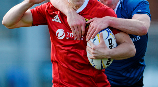 Munster's Paul Buckley is tackled by Leinster's Tommy O'Brien
