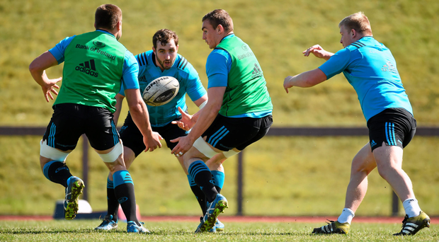 Munster's Tommy O'Donnell off-loads to team-mate CJ Stander during training on Tuesday. Photo: Sportsfile