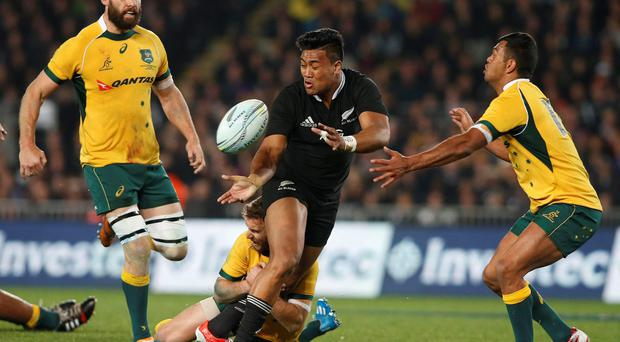 Julian Savea (C) of New Zealand's All Blacks gets the ball away while being tackled by Pat McCabe (bottom) of Australia's Wallabies during their second Bledisloe Cup rugby championship match at Eden Park in Auckland