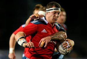 Robin Copeland, Munster, is tackled by Jarrad Hoeata, Cardiff Blues