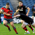 Duncan Casey, Munster, is tackled by Nathan Fowles, Edinburgh