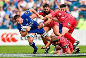 Dominic Ryan, Leinster, is tackled by Rory Pitman, left, and Ken Owens, Scarlets