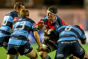 Robin Copeland, Munster, is tackled by Gareth Davies, Dan Fish and Manoa Vosawai, Cardiff Blues