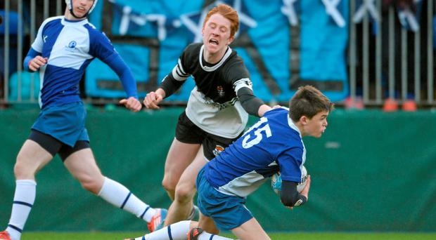 Mark Delaney, St. Andrew's College, is tackled by Nick Hibberd, Newbridge College