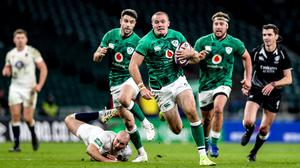 Jacob Stockdale of Ireland beats the tackle of Dan Robson of England on the way to scoring his side's first try during the Autumn Nations Cup match between England and Ireland at Twickenham last November. Photo: Matt Impey/Sportsfile