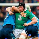 Tommy O'Donnell, Ireland, wrestles with Francesco Minto, left, and Alessandro Zanni, Italy, after the ball was played away from a ruck