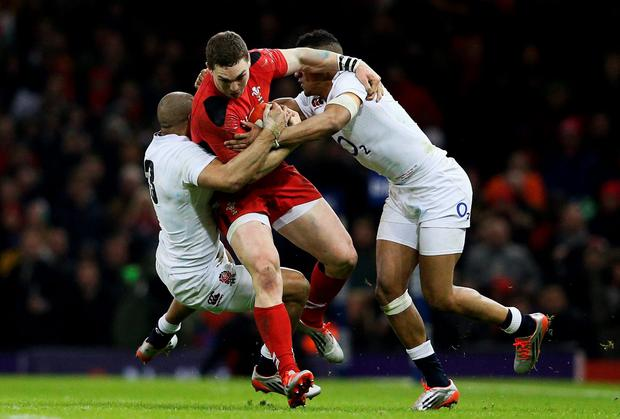George North of Wales is tackled by Jonathan Joseph and Anthony Watson of England during the RBS Six Nations match between Wales and England at the Millennium Stadium