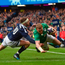 Keith Earls scores Ireland's first try despite the tackle of Finn Russell. Photo: Ramsey Cardy