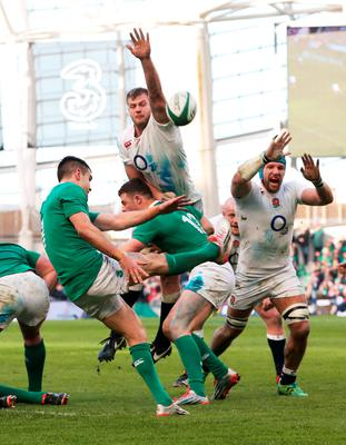 Ireland's Conor Murray clears the ball upfield despite the attentions from England's George Kruis and James Haskell  during the RBS Six Nations match between Ireland and England at the Aviva Stadium