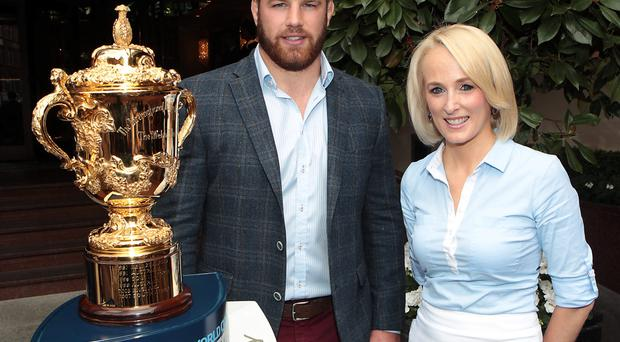 TV3 presenter and Irish Independent columnist Sinead Kissane pictured alongside Ireland international Sean O'Brien with the William Webb Ellis trophy in Dublin yesterday