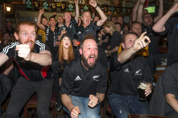 New Zealand All Blacks Fans celebrate a try while watching the match at Paddy Cullens pub in Ballsbridge