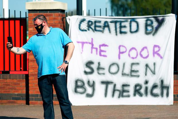 A member of the public poses for a photo in front of a sign posted by football fans opposing the European Super League outside Old Trafford. Photo: PA Wire
