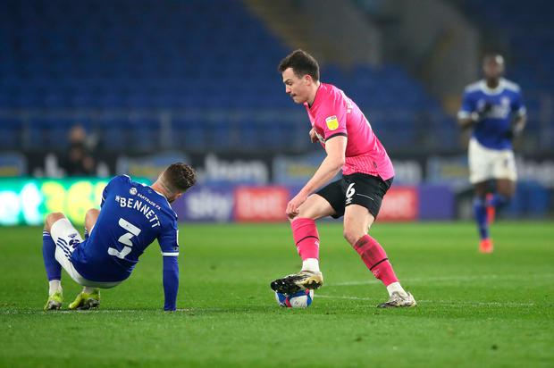 Derby County's George Edmundson with the ball as Cardiff City's Joe Bennett (left) goes down injured in a potentially serious blow to Mick McCarthy's side during the Sky Bet Championship match at the Cardiff City Stadium. Photo: Nick Potts/PA Wire