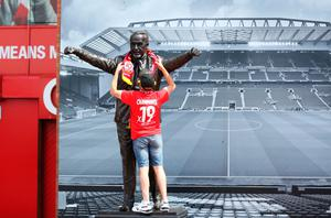 Liverpool fan Anthony Furns wraps a scarf around the Bill Shankly statue outside Anfield. Photo: Martin Rickett/PA Wire