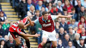 Burnley's Lukas Jutkiewicz (right) holds off Sunderland's Wes Brown during the Barclays Premier League match at Turf Moor, Burnley.