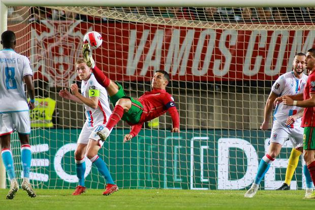 Portugal's Cristiano Ronaldo, center, attempts to score with an overhead kick during the World Cup qualifying win over Luxembourg