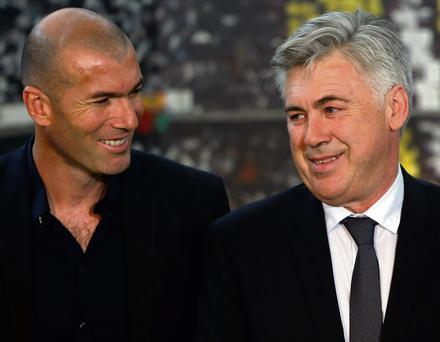 New Real Madrid coach Carlo Ancelotti (R) smiles next to former soccer player Zinedine Zidane