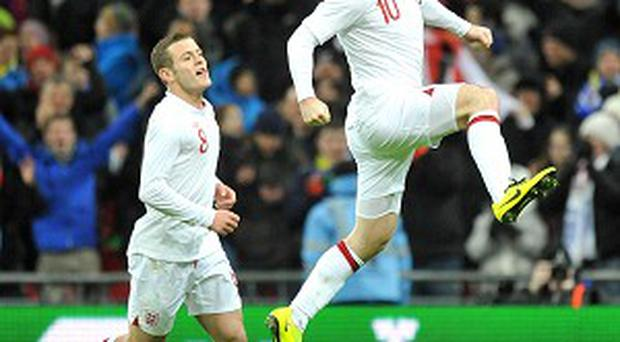 Jack Wilshere, left, would love to play with Wayne Rooney, right, for club as well as country