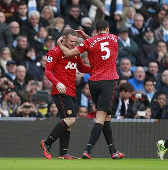 Rio Ferdinand, right, thinks Waye Rooney, left, should stay at Manchester United
