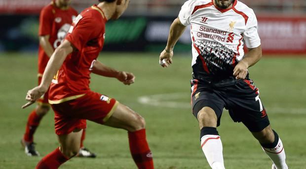 Liverpool's Luis Suarez is challenged by Atit Daosawang of Thailand during the friendly match in Bangkok
