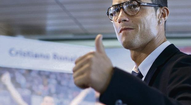 Cristiano Ronaldo greets the media after signing a contract renewal for Real Madrid
