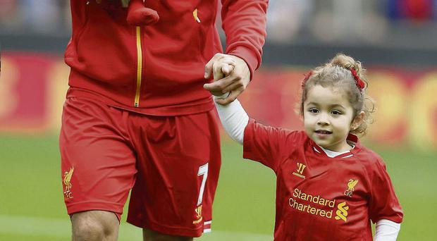 Luis Suarez on the pitch with his daughter Delfina, whose name is an anagram of Anfield, and nine-day-old son Benjamin before the Crystal Palace match