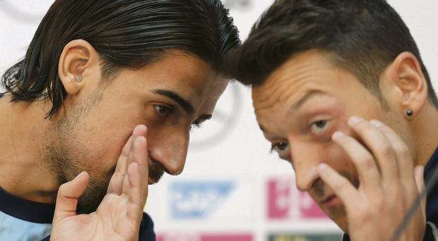Sami Khedira and Mesut Ozil attempt to have a private chat at yesterday's press conference in Cologne