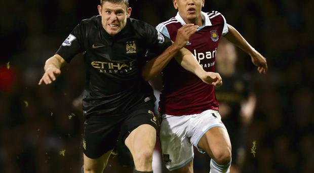 James Milner and Ravel Morrison in a race for the ball