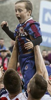 10-year-old Jack Cummins is held aloft by Anto Flood after his goal against Sligo