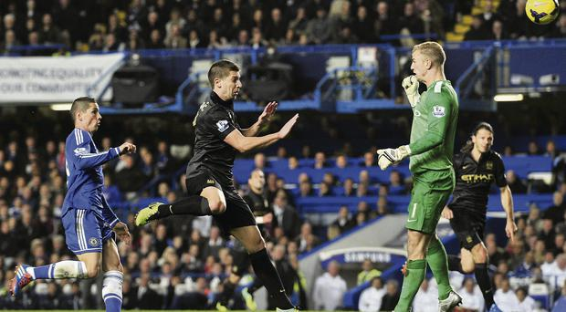 Manchester City's Serbian defender Matija Nastasic (2nd L) heads the ball back past his own goalkeeper Manchester City's English goalkeeper Joe Hart, allowing Chelsea's Spanish striker Fernando Torres (L) to score the winning goal