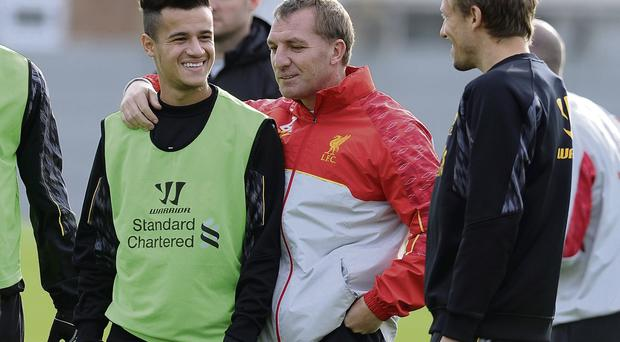 Liverpool manager Brendan Rodgers puts his arm around Philippe Coutinho who has recovered from injury in time to face Arsenal tomorrow