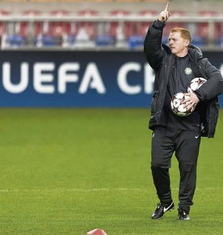Celtic manager Neil Lennon addresses his players during a training session before their Champions League group H soccer match against Ajax