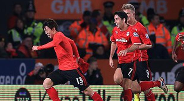 Kim Bo-Kyung, left, celebrates scoring his team's second goal