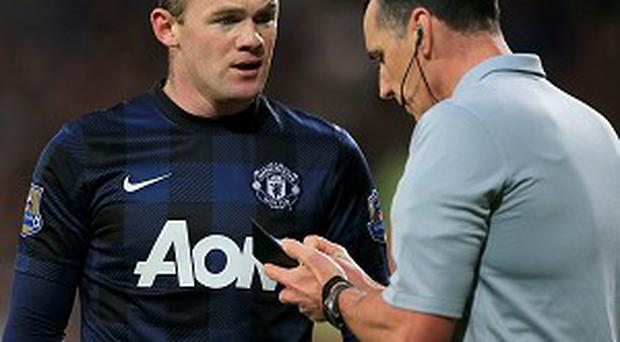 Wayne Rooney, left, is booked by Neil Swarbrick