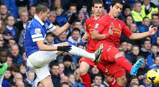 Kevin Mirallas, left, was only booked for his high tackle on Luis Suarez, right