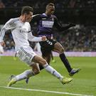 Real Madrid's Gareth Bale gets the better of Real Valladolid's Zakarya Bergdich and, below, he celebrates his hat-trick with the match ball