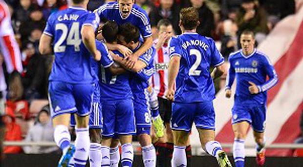 Eden Hazard, obscured, is mobbed by team-mates after scoring Chelsea's second