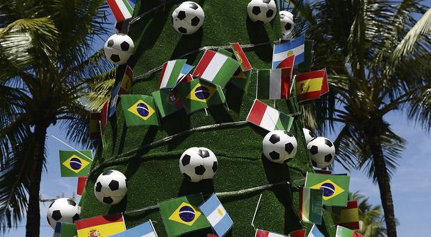 A replica of the World Cup trophy adorns the top of a Christmas tree decorated with footballs and national flags in the grounds of the Costa do Sauipe resort, where the draw for the finals will be made today. Clive Mason/Getty Images