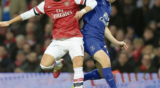 Everton's Seamus Coleman (right) and Arsenal's Mesut Ozil battle for the ball