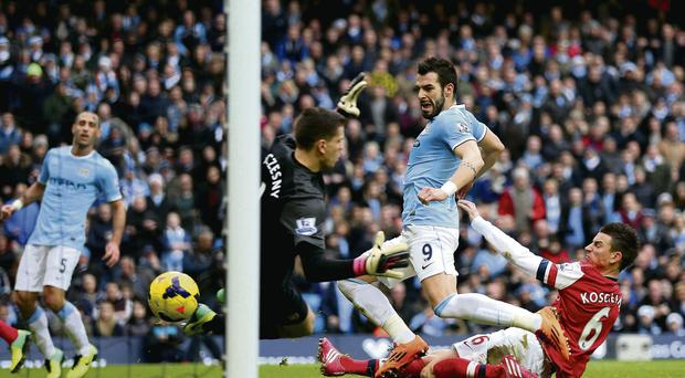 Arsenal's Laurent Koscielny fails to stop Alvaro Negredo of Manchester City scoring their second goal