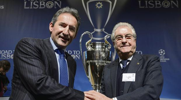 Manchester City football director Txiki Begiristain, left, shakes hands with former FC Barcelona vice-president and grandfather to Gerard Pique, Amador Bernabeu, at the draw for the last 16 of the Champions League