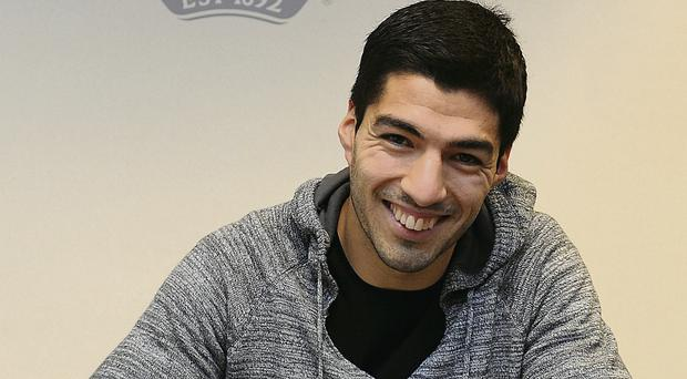 Liverpool's star striker Luis Suarez signs his new long-term contract at the club's Melwood Training Ground yesterday GETTY